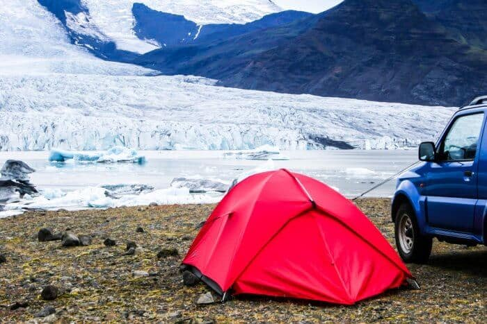 Red tent camping with car in Iceland