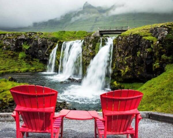 Two red wooden chairs overlooking a beautiful icelanddic waterfalll