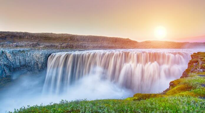 Impressive Detifoss waterfall with the midnight sun behind it.
