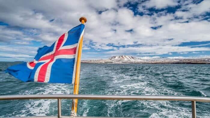 Icelandic flag on boat heading towards island