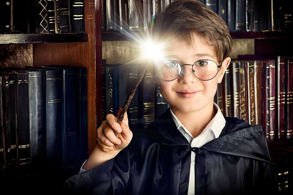 Little boy wearing glasses waving a magic wand