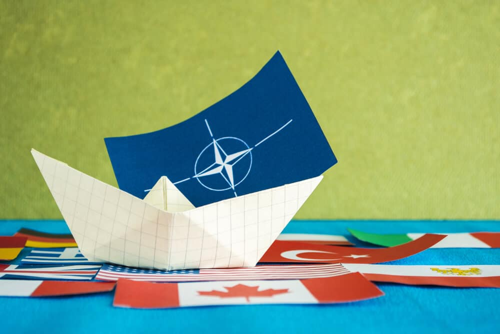 paper ship with the NATO flag and other nations that belong to the alliance just like Iceland