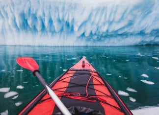 Red sea kayak facing glacier