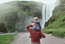 Father with son on his shoulders walking towards Skogafoss waterfall