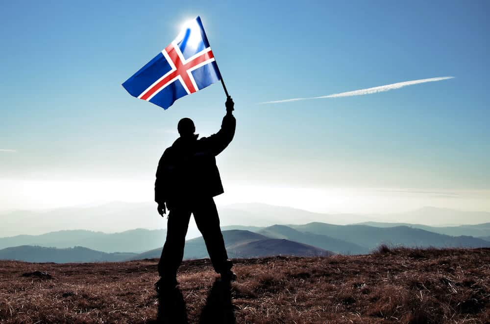 Man holding Iceland flag victoriously