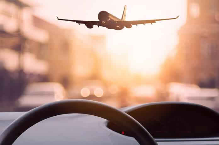 View from car dashboard of plane landing at airport