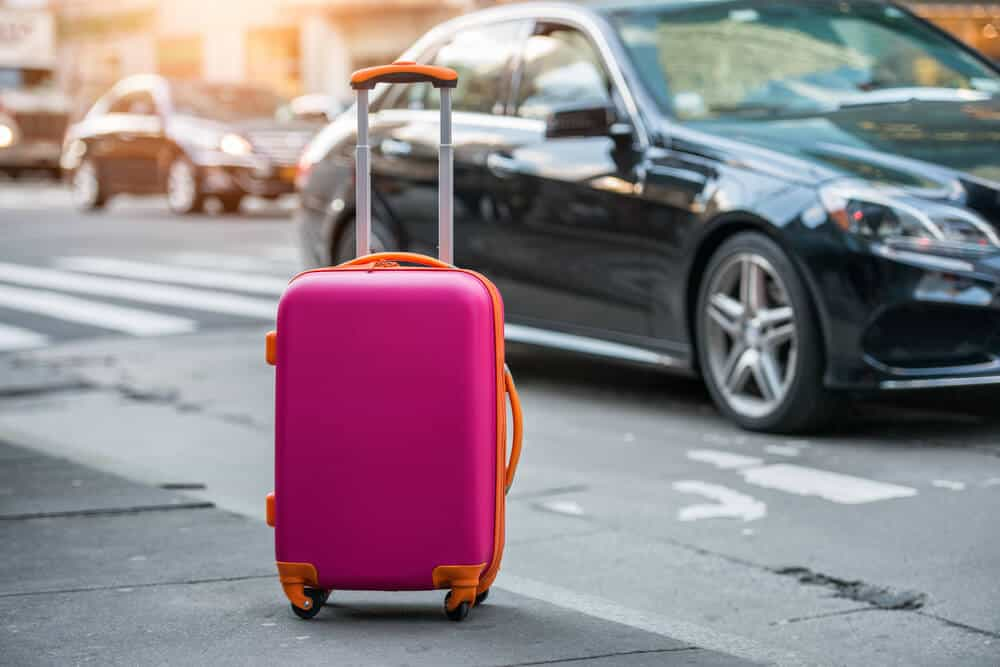 Pink suitcase on the sidewalk at Keflavik Airport