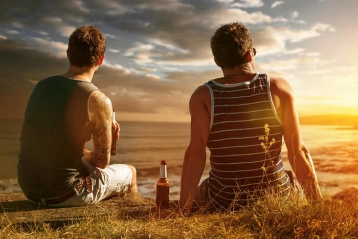 Two best friends enjoy a beer while looking out over the ocean