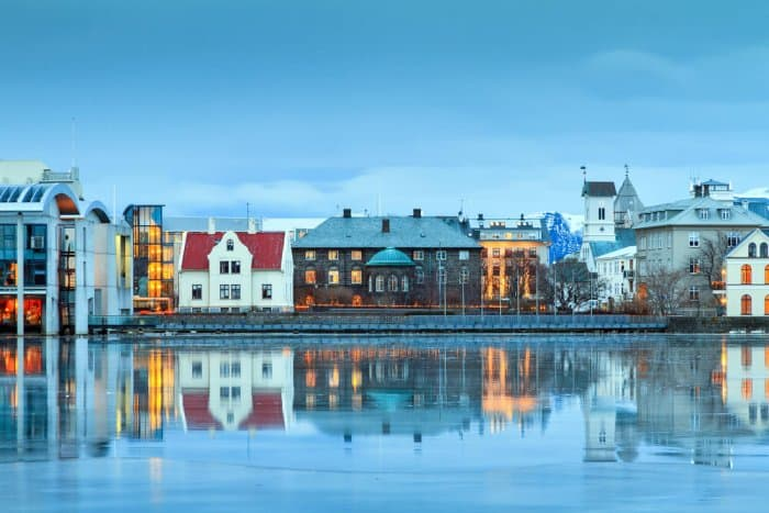 Beautiful reflection of the parliament house Althing of Reykjavik in lake Tjornin at the blue hour in winter
