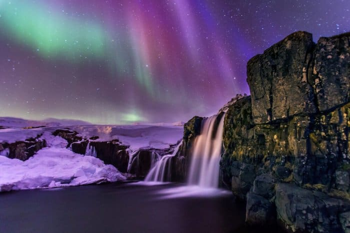 One of Iceand's famous waterfalls with the Northern lights in the background