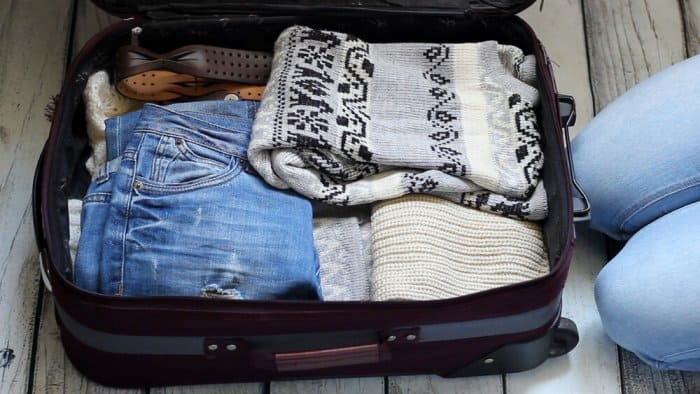 Open suitcase with warm items on the Iceland summer packing list