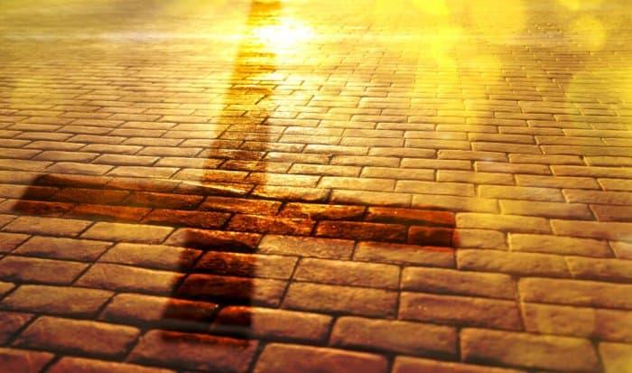 Christian cross spread across sunny cobblestones