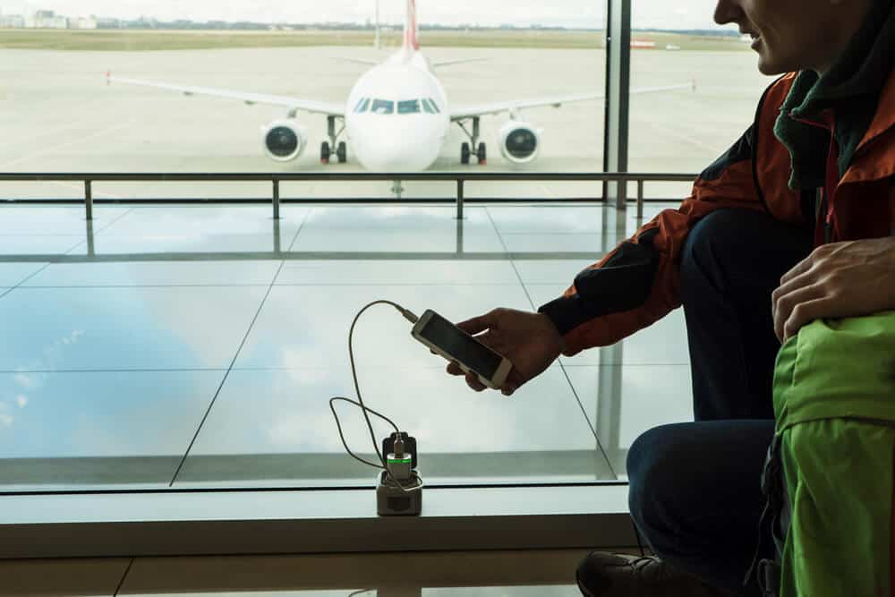 Man charging his phone with a travel adaptor, we included it in our Packing Guide For Reykjavik