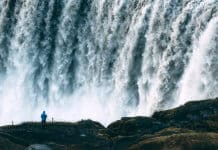 Man dwarfed by the sheer size of Iceland's Dettifoss waterfall, also known as the Beast