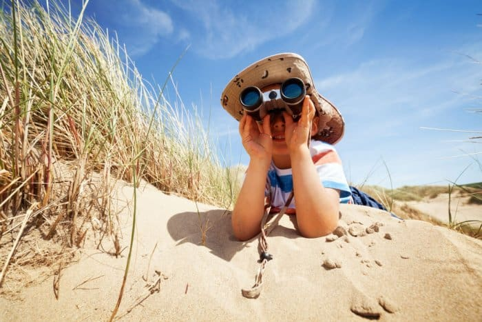 Child looking through binoculars at a beach in Iceland