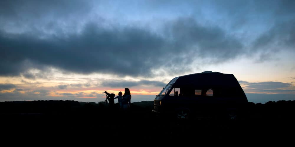 Family with telescope at sunset with a classic VW campervan in Iceland