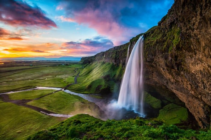 Seljalandsfoss at sunset with colored sky is a main stop on Iceland's Ring Road