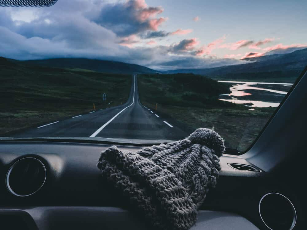 Color streaked sky during Iceland road trip with hat on dashboard
