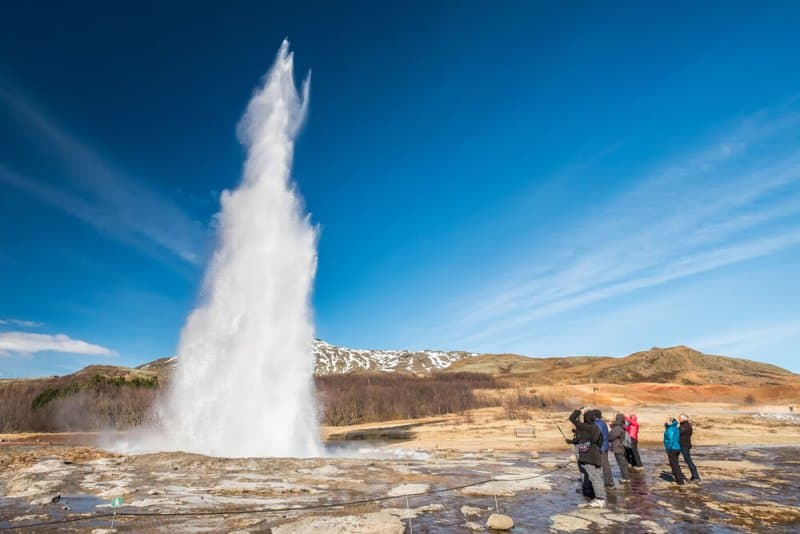 Tourists watching Strokkur geyser eruption in Iceland during best month to visit