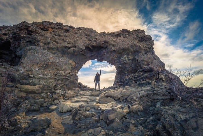 Tourist standing on rocky arch at Dimmuborgir in Iceland