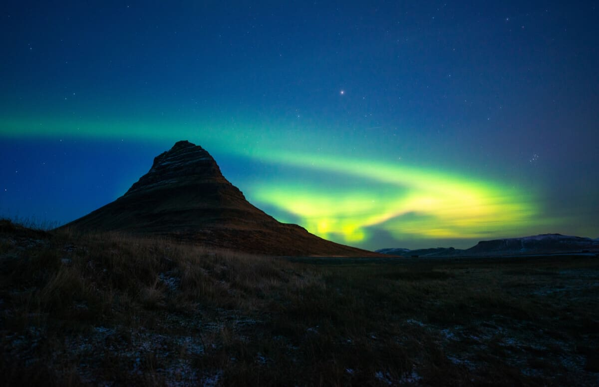 The Northern lights over Kirkjufell mountain and Kirkjufellsfoss waterfall in Snaefellsnes peninsula