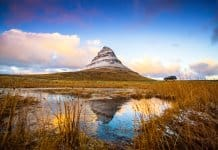 View from the field of Kirkjufell mountain and Kirkjufellsfoss waterfall in Snaefellsnes peninsula