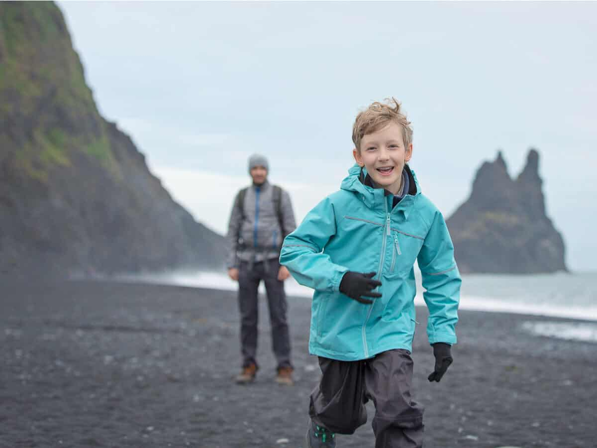 Little boy on beach with father; they have Icelandic family naming customs