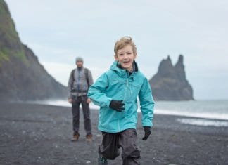 Iceland family vacation with little boy enjoying black sand beaches of Vik