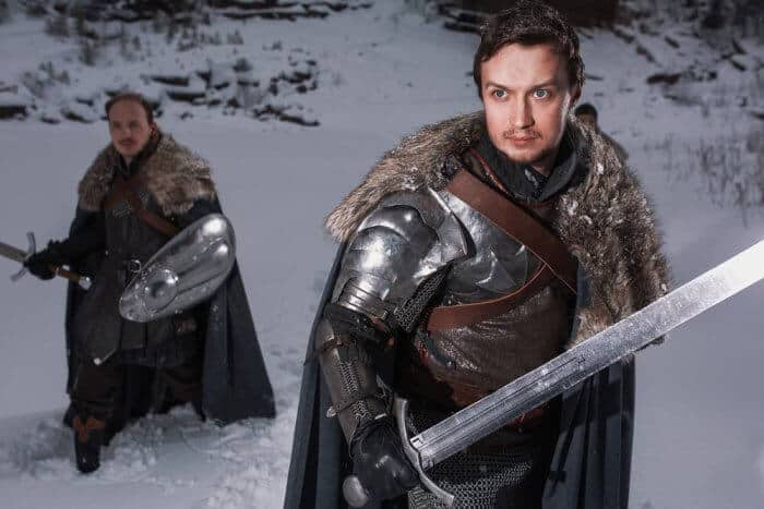 Two man holding swords in a wintery scene dress in medieval clothes for a film