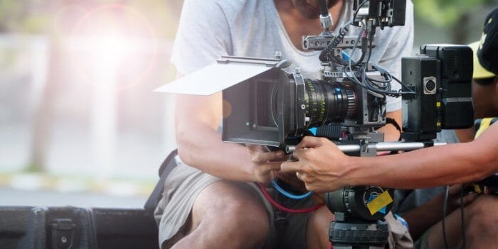 Man holding a professional camera for movie filming