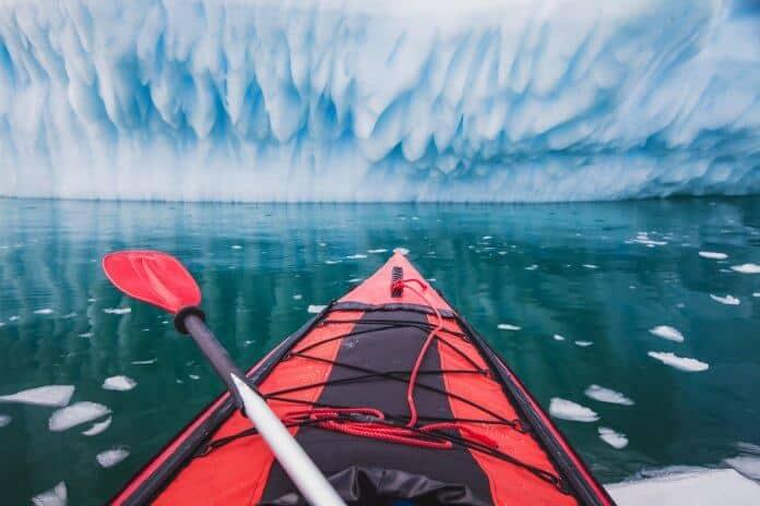 Red sea kayak facing glacier