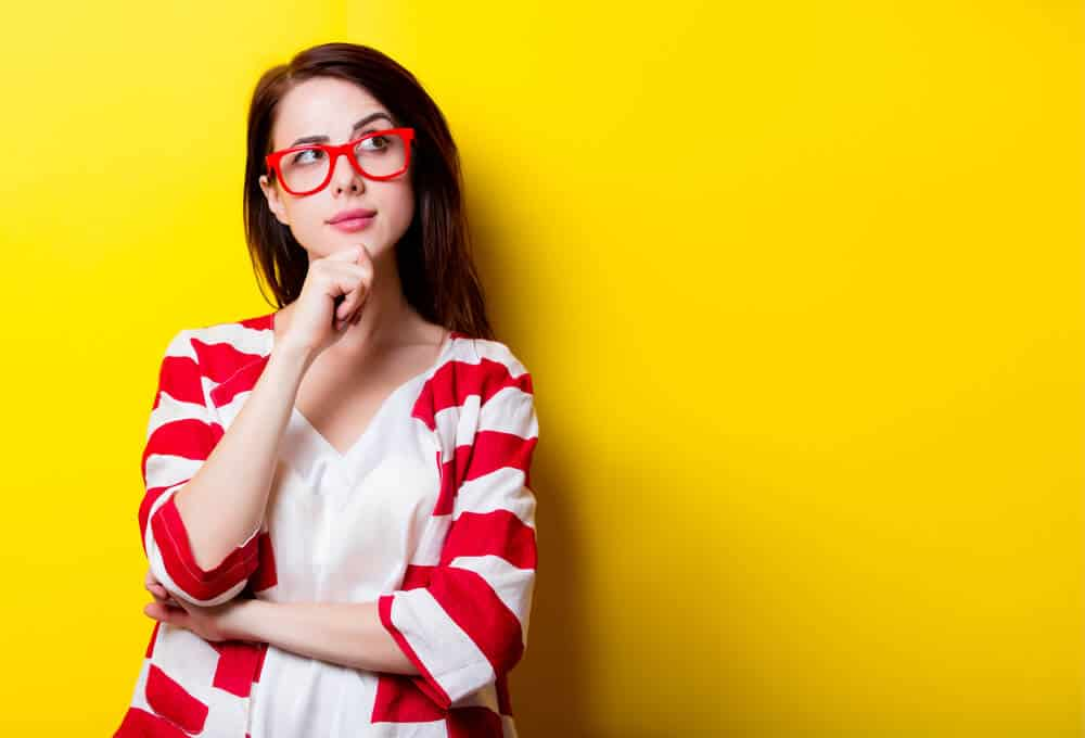 Young woman on yellow background wondering whether or not to visit Iceland