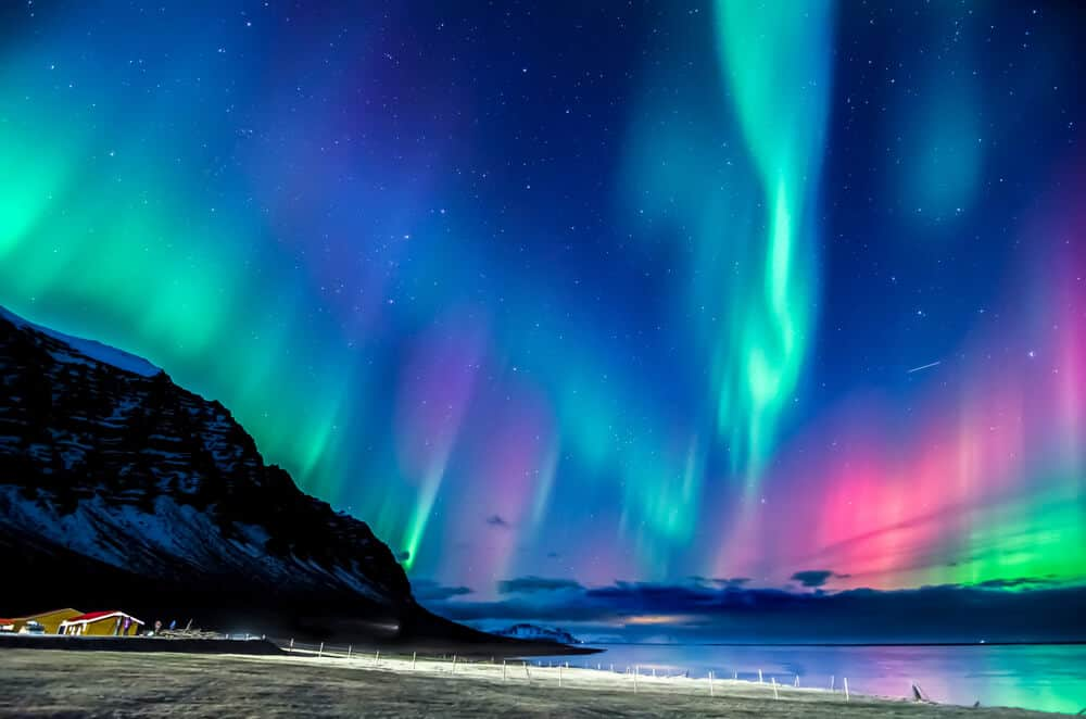 Pink and turquoise Northern Lights that you can see if you purchase the Icelandair travel package during their flash sale