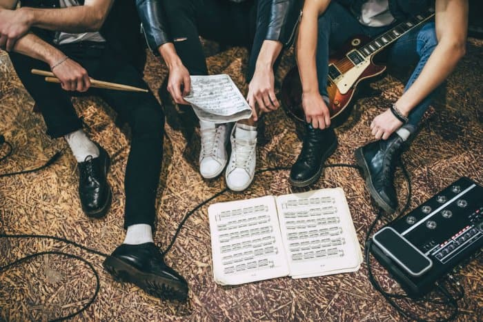 Band recording new album with music on floor