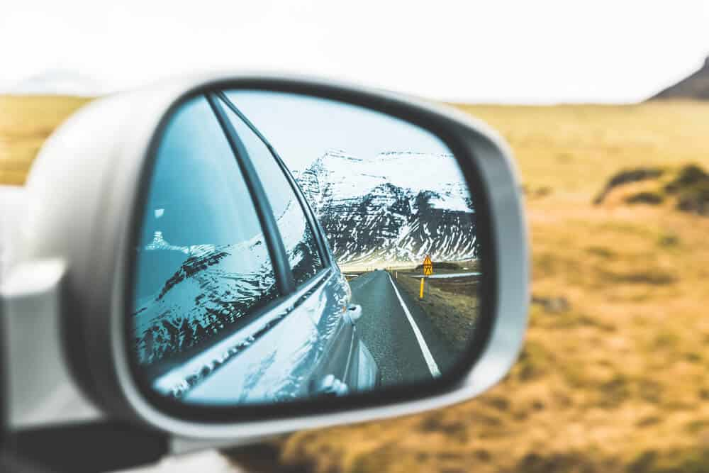 A rearview mirror showing mountains on Iceland's Ring Road