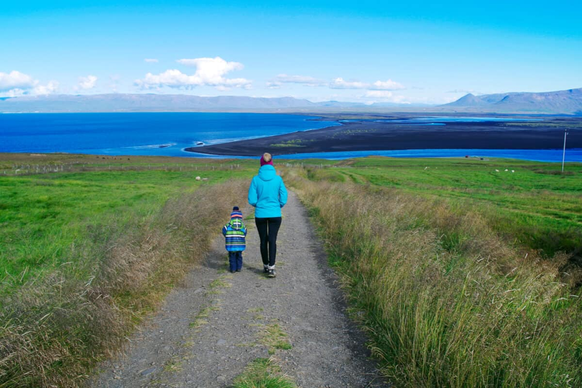 During and Iceland family vacation mother and son walking among the fjords and grass