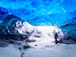 tourist visiting an Ice cave inside of a glacier in Iceland